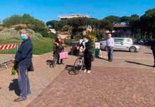 Gente in fila, rispettosa delle normative, all'ingresso del mercato alimentare