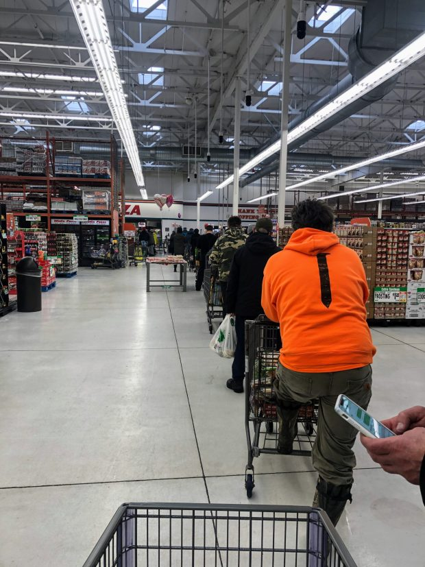 Grocery store with long line of people waiting to check out.
