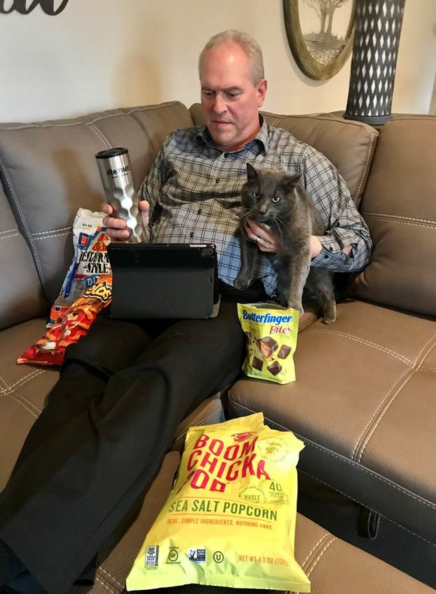 man working from home with snacks and cat