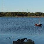 ein kleiner See, im HIntergrund Wald auf dem See ist ein kleines Segelboot verankert