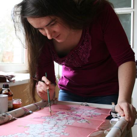 Elizabeth Grinberga painting silk scarf in her studio