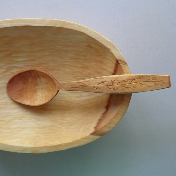 A hand-carved, sustainably-harvested, willow serving spoon, featuring a live edge handle and wild chamomile carving at RivenJoiner.com.