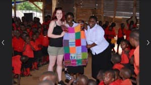 Miss Logan presenting the Riverbank blanket to Beatrice, the head teacher of Bezallel School