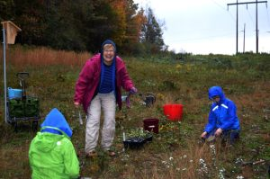 Volunteer Marty MacCleery helps Goodwillie students plant natives.