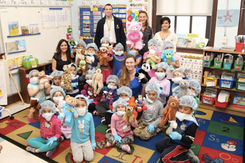 Kindergarten teacher Anselma Jimenez (seated far left with her students) and Teacher Assistant Marisa Mullane (middle in blue) with their kindergarten students. Also pictured in the back: L-R Dr. Noah Jablow, Kristi Landowski, MPH and Dr. Anupa Dalel from Stony Brook Trauma Center and Hospital. Courtesy photo