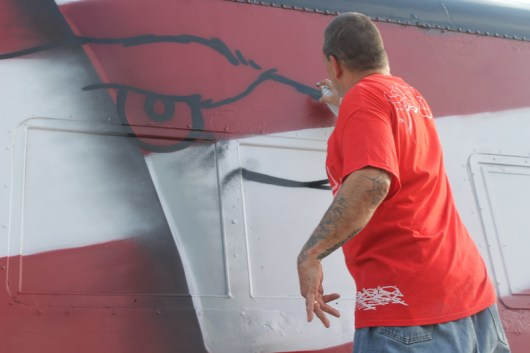 Duster, UA at work sketching out the mural on a railroad car this afternoon at the Railroad Museum of L.I. in Riverhead.Photo: Denise Civiletti