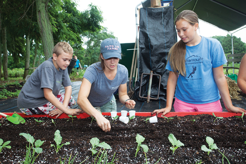 Young Farmers Camp coordinator Lucy Senesac plants seeds with Rudy Bruer, 10, of Mattituck and Julia Galasso, 12, of Westhampton. (Credit: Katharine Schroeder)