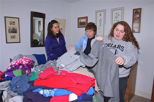 BARBARAELLEN KOCH PHOTO  |  Nir Silva of Hampton Bays (from left), Virginia Lemmers and Nina Keller, both of South Jamesport, sort through the donated Items in Ms. DeVito's bedroom Saturday afternoon.