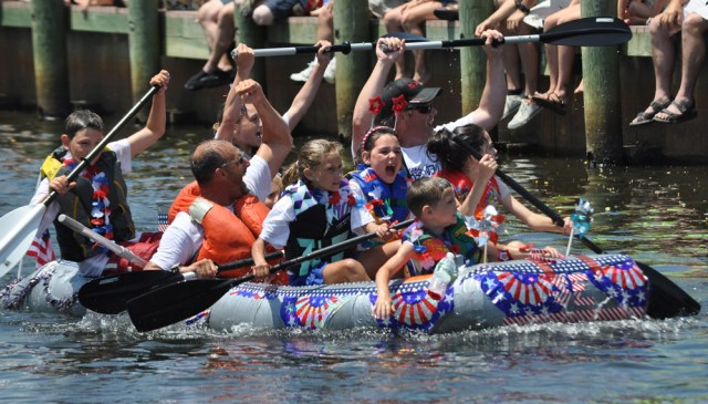 The crew of the Speedie Edie celebrates its victory down the home stretch of the team's heat of the Fifth Annual Cardboard Boat Race in downtown Riverhead Sunday. (Credit: Grant Parpan)