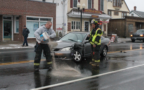 PAUL SQUIRE PHOTO | A Jamesport firefighters spreads absorbent material to soak up vehicle fluid at the scene of a two-vehicle crash Monday afternoon.