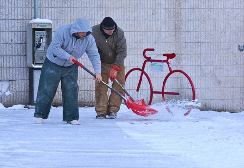 BARBARAELLEN KOCH PHOTO | Riverhead building and grounds workers shoveling downtown by the River and Roots Community Garden Tuesday morning.