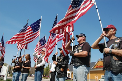 Members of the Patriot Guard Riders hold flags during Monday's press conference.