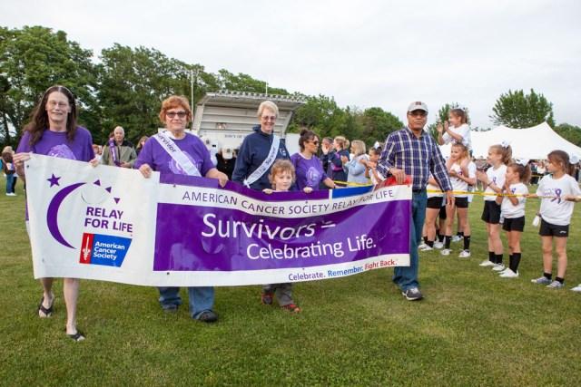 Survivor Sam Duffy, center, leads the survivor walk. (Credit: Katharine Schroeder)