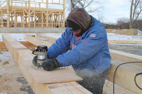 PAUL SQUIRE PHOTO   Erek Berntsen cuts wood at a construction site near the Glass Greenhouse in Jamesport.