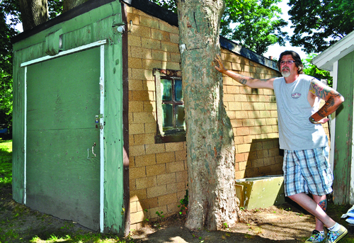 GIANNA VOLPE PHOTO   Richard Hardt next to the garage he said his great-grandfather Mervin Baker assembled with lumber left over from the building of Brecknock Hall in Greenport.