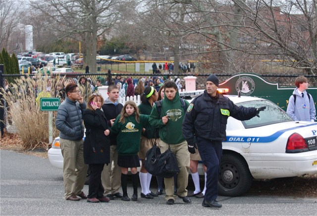 A Riverhead police officer leads Mercy students from the school on Jan. 14. (Credit: Barbaraellen Koch)