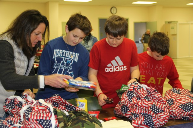 Southold Elementary teacher Patty Mellas helps students Ben Ward, Aidan Russell, both 11, and Tate Klipstein, 10, pack care packages for veterans. (Credit: Carrie Miller)