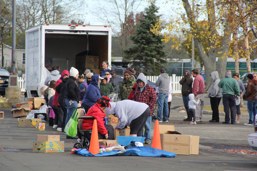 CARRIE MILLER PHOTO | About 150 people lined up beside the Peconic riverfront Friday afternoon to receive groceries from Lighthouse Mission.