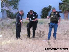 Officers check a handgun they found after the foot shooting and foot pursuit. Epicenter News photo