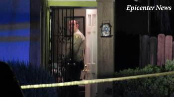 A deputy stands in the doorway of a residence where the officer involved shooting occurred. Miguel Shannon / Epicenter News photo