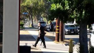 A Hemet Police officer returns to his vehicle with his shotgun. Gary Rainwater photo