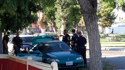 Officers search a vehicle owned by one of the detained subjects. Gary Rainwater photo