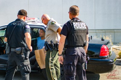Officials discuss the stolen vehicle and the large bag of marijuana that was found inside the car. John Strangis photo
