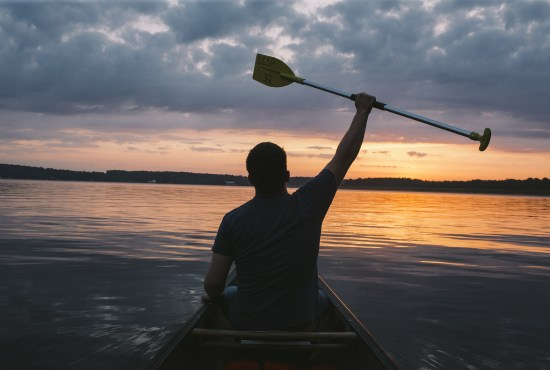 silhouette of man holding up paddle on lake during sunset