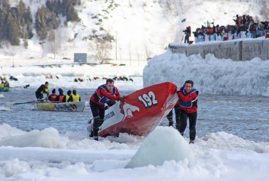 Racers pull their canoe onto the ice. Photo credit: Quebec Winter Carnival