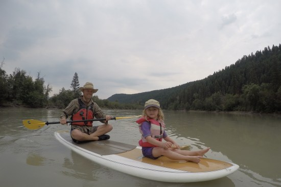 kid friendly river trip: dad and child sitting on a paddleboard on the Columbia River
