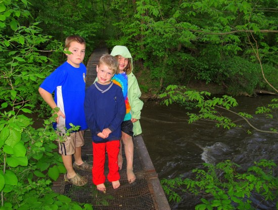 kids standing on footbridge after kayaking on mother's day