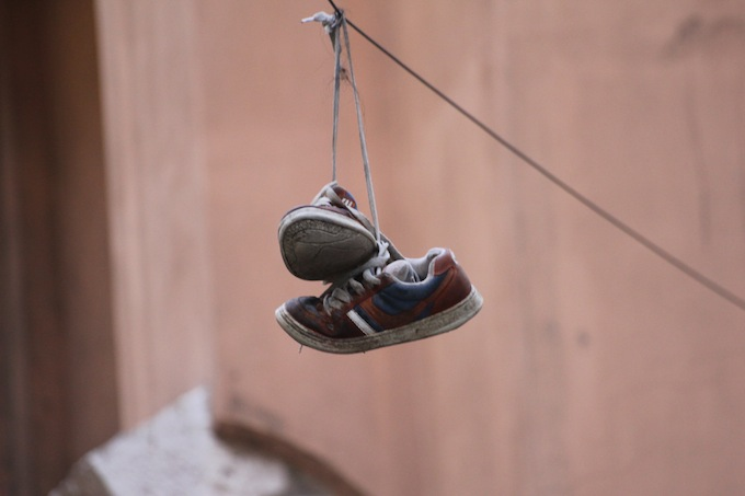 What is the reason for throwing shoes over a power line?