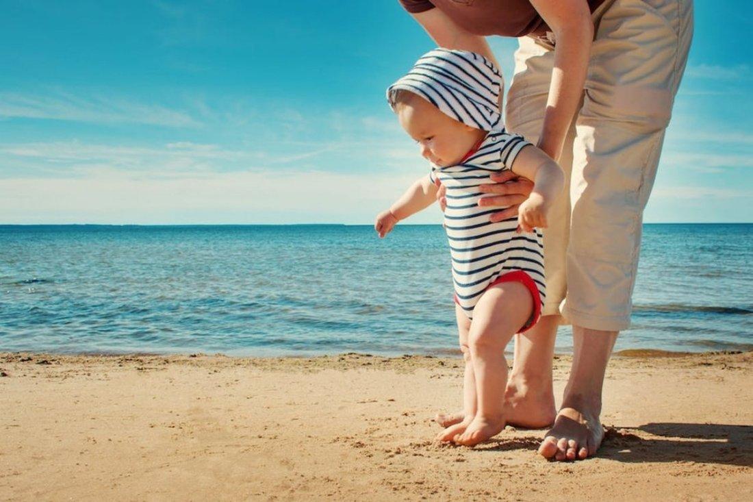 Liguria in primavera neonato in spiaggia che prova a camminare