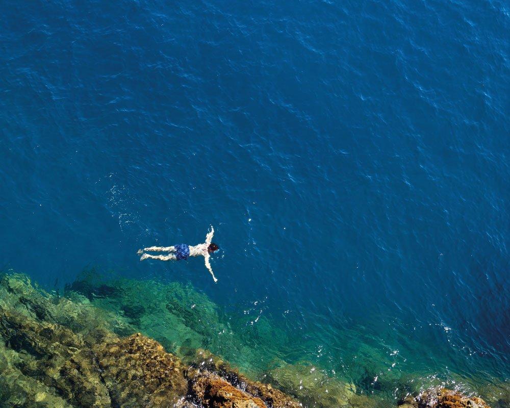 Uomo che nuota in Liguria al mare