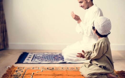 A man with his child praying after finishing Salat