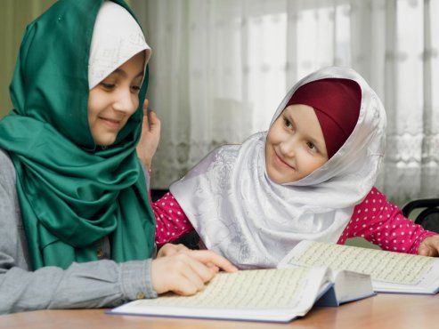 Two Muslim girls memorizing the Quran with each other