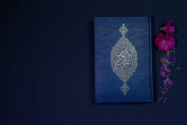 A copy of the Quran beside some flowers