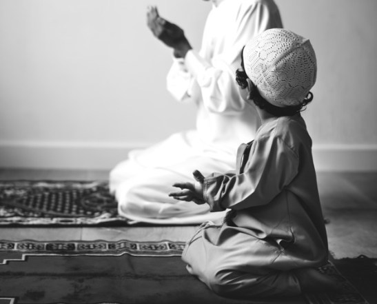 A kid learning how to pray