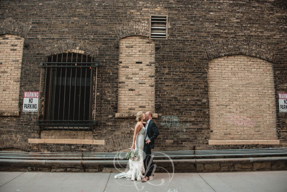 Bride and groom kissing in alley