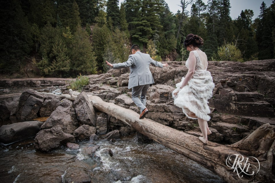 bride and groom walking across log