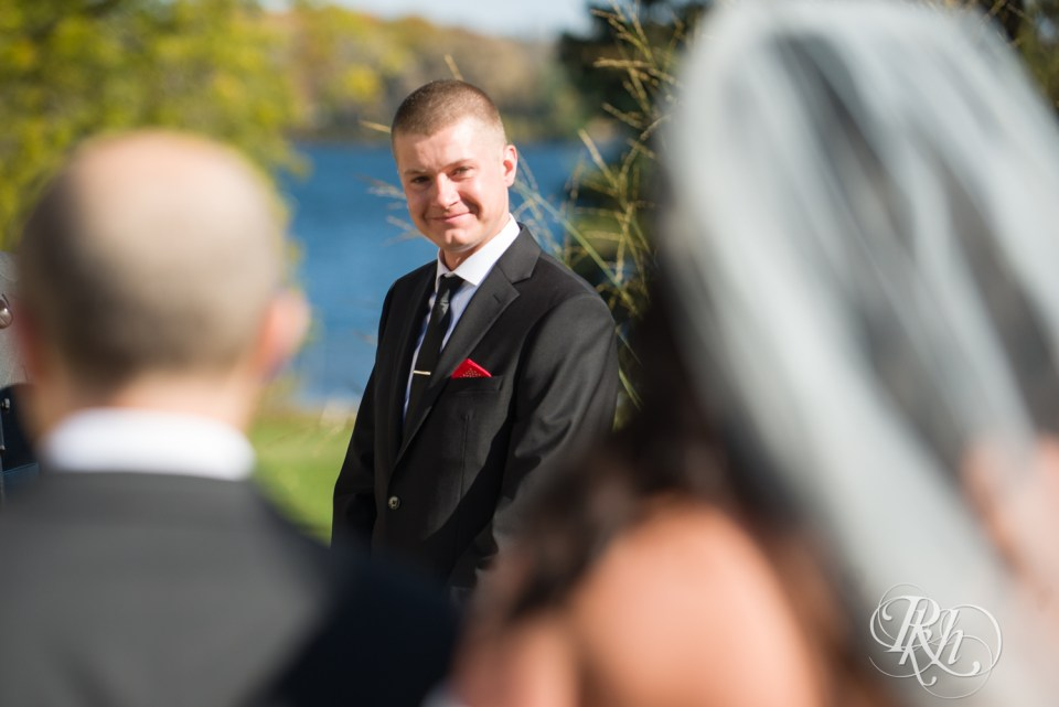 Groom seeing bride in aisle