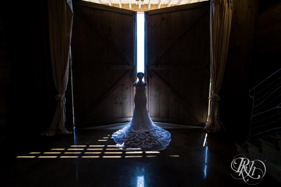 Bride opening barn doors at barn wedding