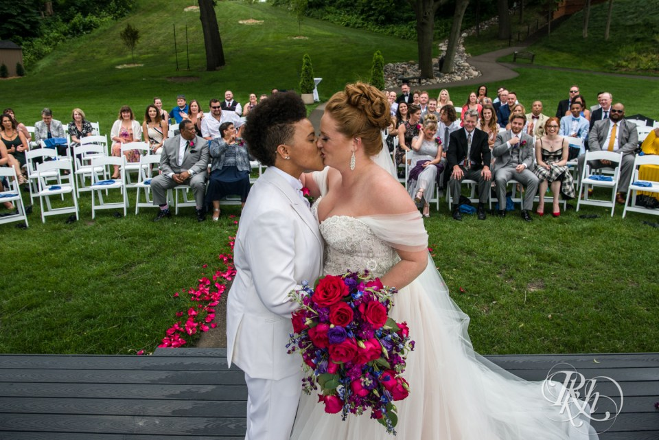 Lesbian wedding first kiss with guests in background