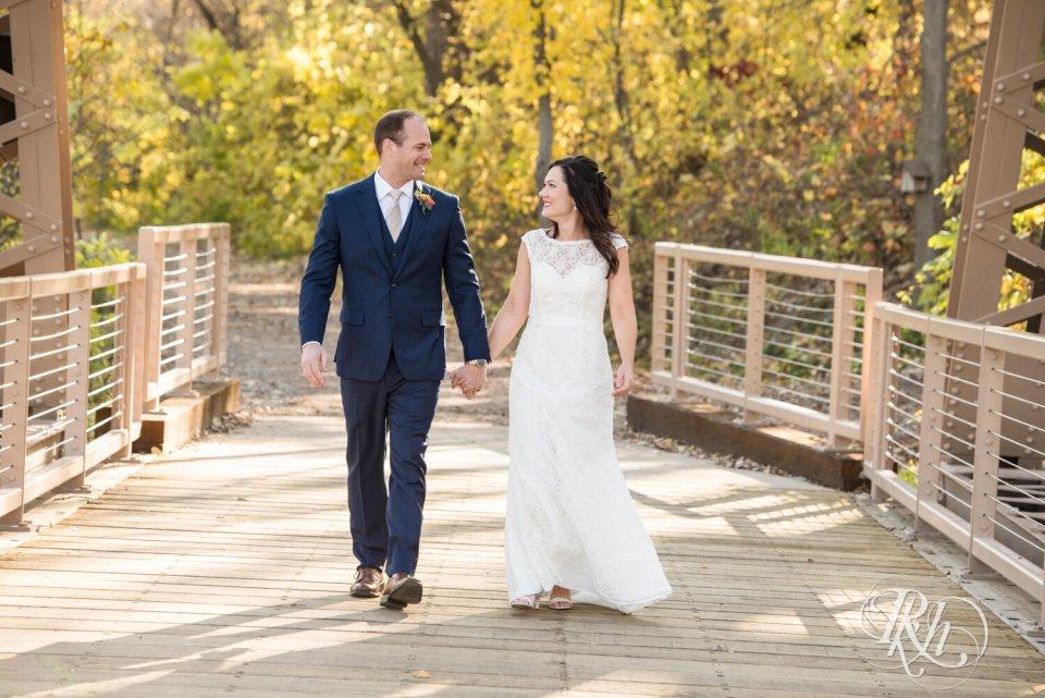 Bride and groom walking on bridge