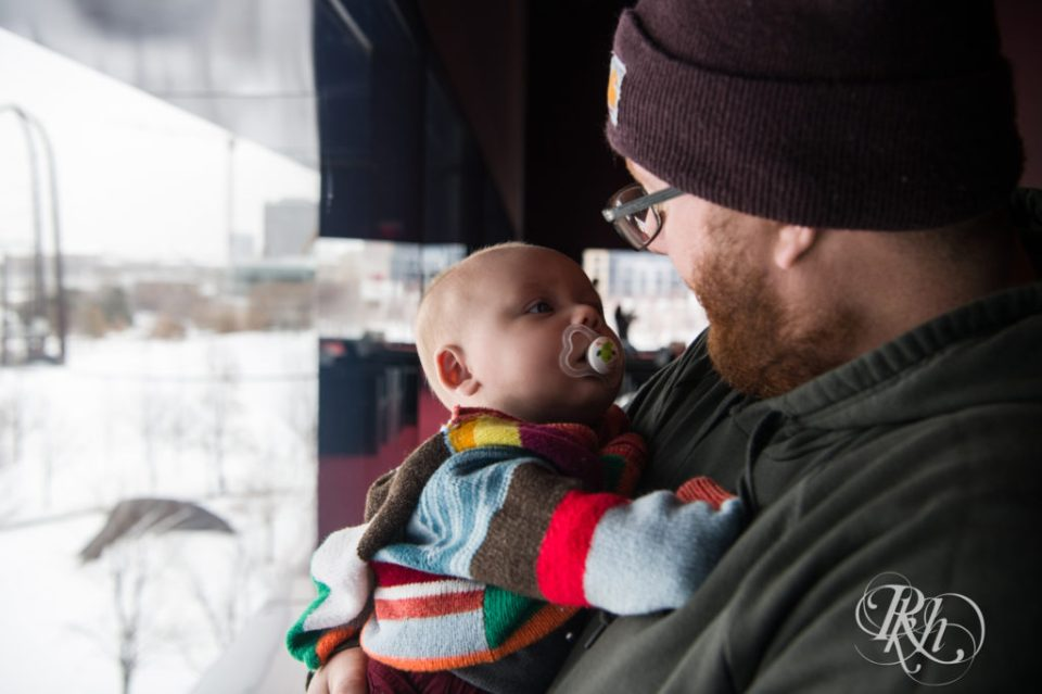 Baby looking at father in winter hat