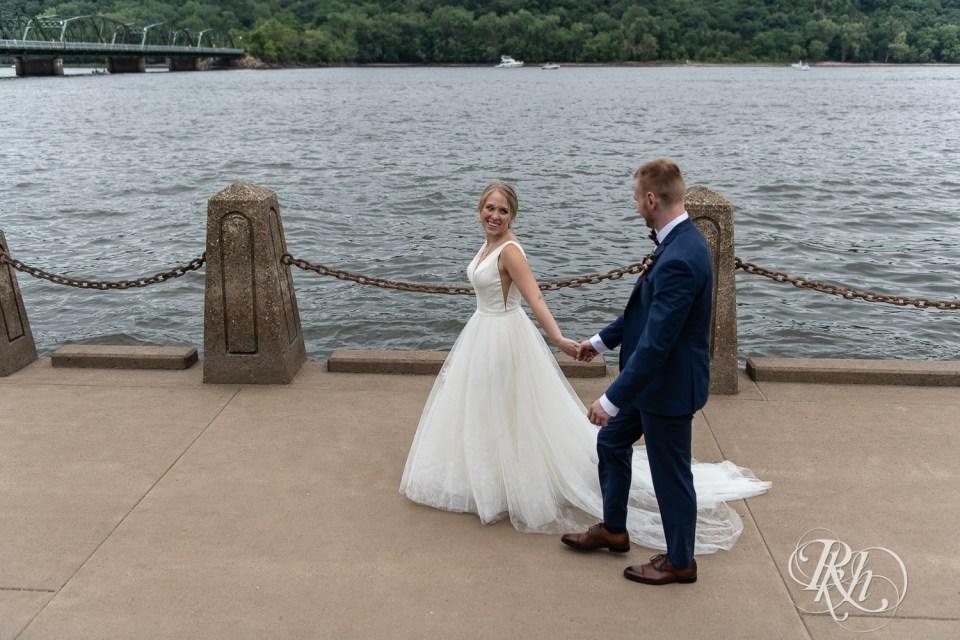 Bride and groom walking along river