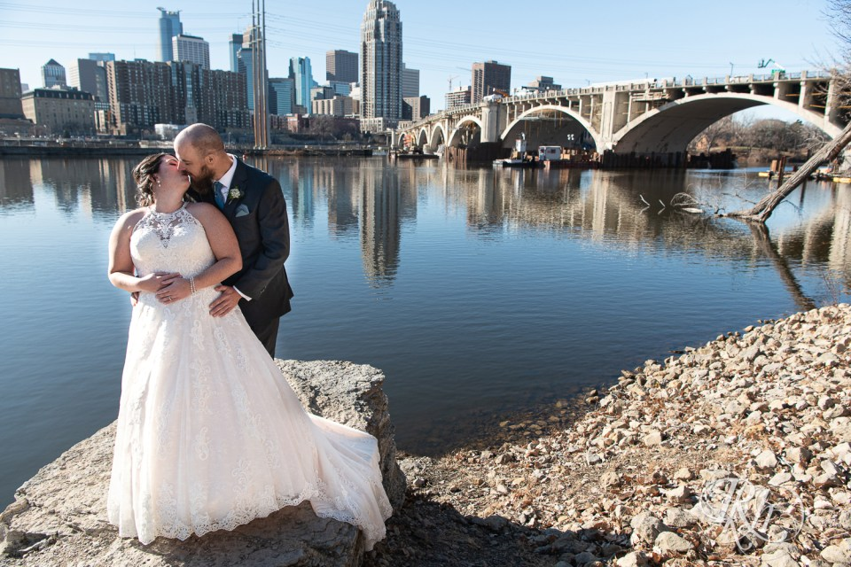 bride and groom kiss with city in background