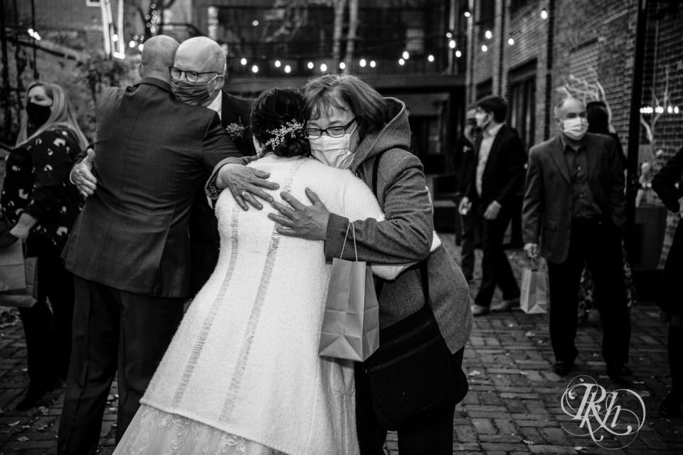 november wedding bride and groom hugging people