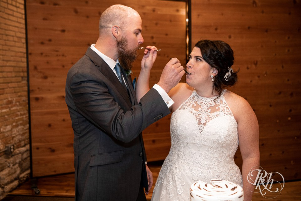 november wedding bride and groom feeding each other cake