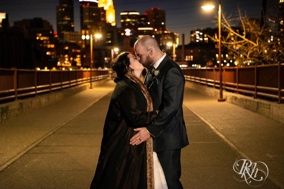 bride and groom kiss on bridge city lights